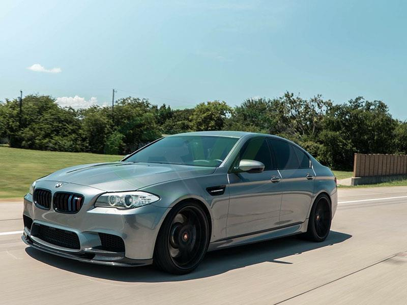 A grey BMW F10 M5 in rolling shot with a 3D style front lip spoiler